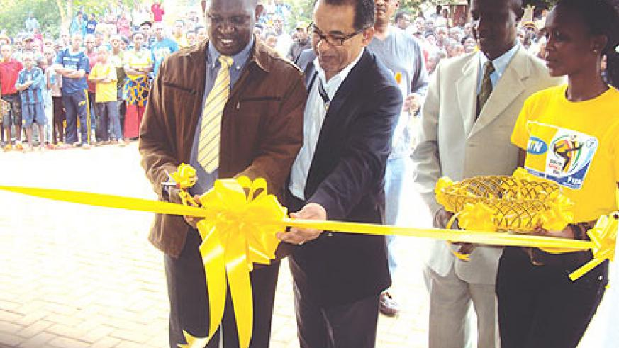 Jean Marie Makombe (L) helped by MTN officials to officially open the service centre. (Photo/ S.Rwembeho)