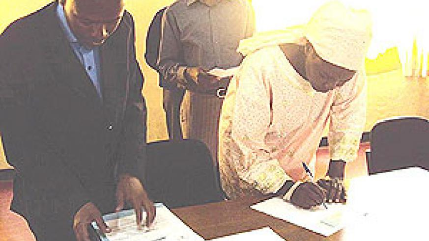 Families of victims sign for their compensation. (Photo: B. Mukombozi)