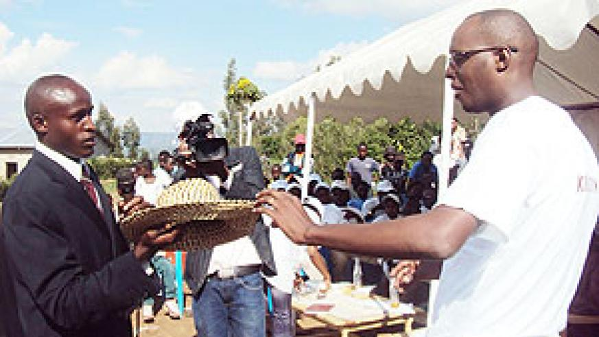 Patrick Makuza, the club president receives one of the many gifts from Ernest Mukunzi, the head of the orphanage. (Photo: D. Sabiiti)