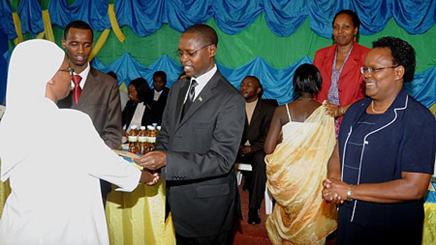 Minister Mathias  Harebamungu handing over the cheque to the administrator of one of the winning schools yesterday ( Phot F. Goodman )