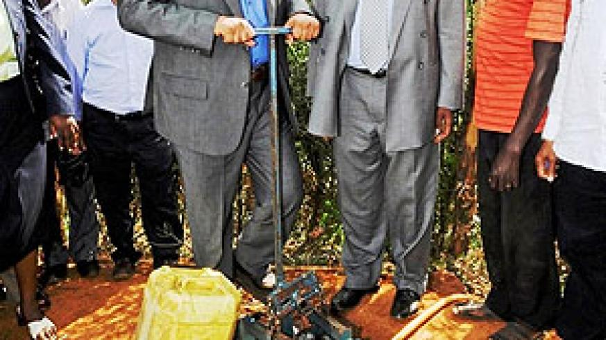 Ambassador Abderrahim Ould Hadrami trying a water pump at Murama school, while Dr. Charles Murigande looks on. (Courtesy photo)