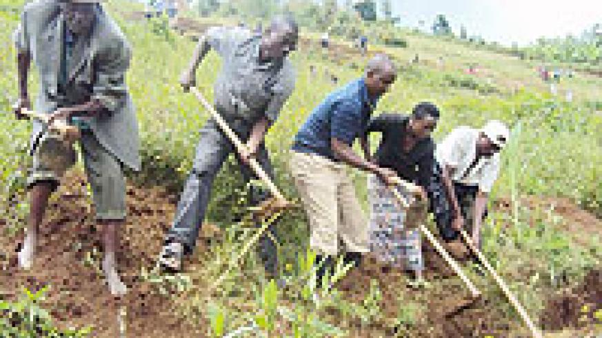 LEADS THE WAY: Karongi mayor Bernard Kayumba (centre) leads residents in digging up a trench to cub soil erosion. (Photo: S. Nkurunziza)
