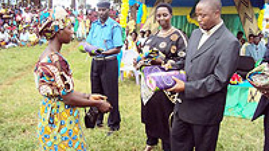 Dr. Léonard Kagabo hands over a reward to one of the Mothers. On his right Vice Mayor Anita Mutesi looks on. (Photo: S. Rwebeho)
