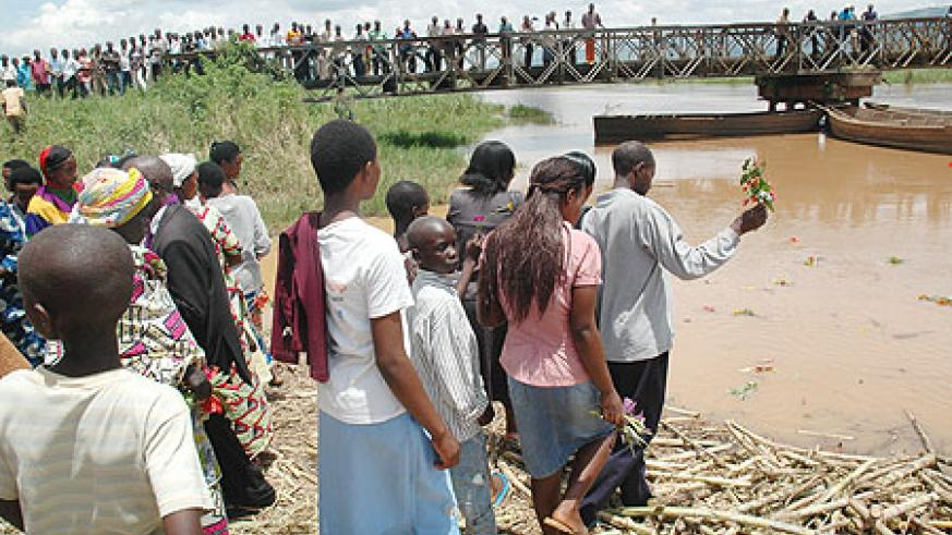 Residents of Kanzenze in Bugesera District throw flowers in Akagera river on Wednesday to honour their beloved ones who were dumped in the river during the 1994 Genocide against theTutsi.