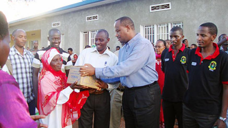 WDA Director General, Albert Nsengiyunva, hands over some of the  donations to one of the widows. (Courtesy photo)