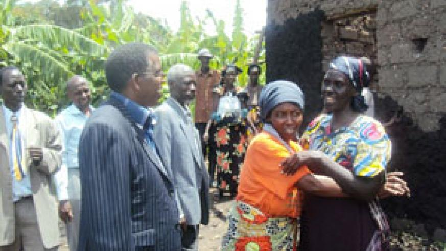 Pelagie Nirere (R), gets a hug of peace from the mother of those who destroyed her house during the genocide as others look on. (Photo: D. Sabiiti)