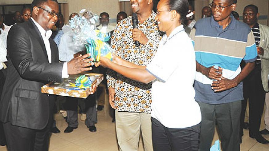 Local Government Minister,  James Musoni,(C) presents gifts to the Permarnent Secretary of Local Government and Rural Development of Malawi Patrick Kabambe(L). (Photo J. Mbanda)