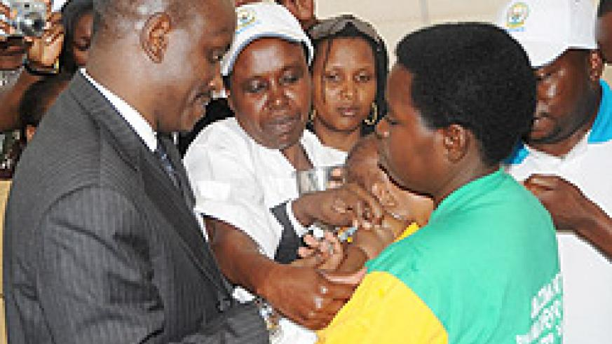 The Minister of Health Dr. Richard Sezibera immunises a child as he launched the Mother-Child Health week in Kamonyi District yesterday. (Photo; J. Mbanda)