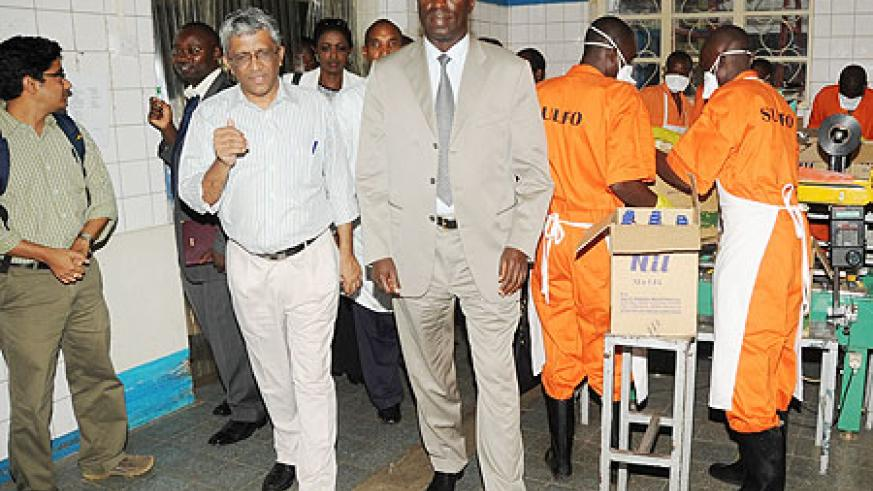 The Minister of Labour, Anastase Murekezi (L) touring SULFO Industries premises accompanied by the company's Director H. Dharmarajan (R). (Photo J. Mbanda)