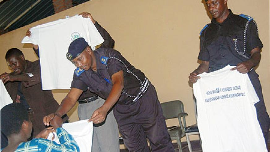 Supt. Alex Rutabayiro, the Karongi District Police commander (C) leads other officers in distribution of t-shirts as part of the 10th anniversary.