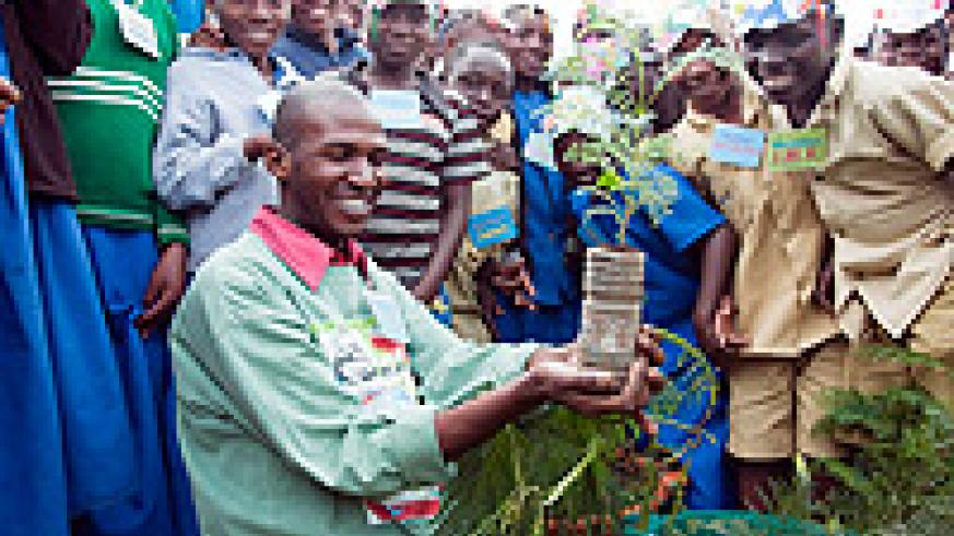 Eric Mutabazi shows the students a seedling of the tree during the exercise (Courtsey Photo)