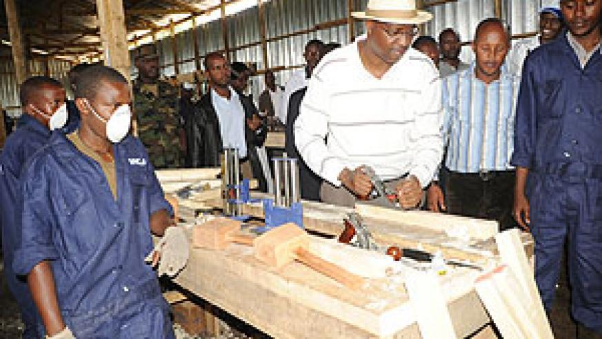 Youth Minister, Protais Mitali tries  out some of the  workshop equipment at Iwawa.(Photo J Mbanda)
