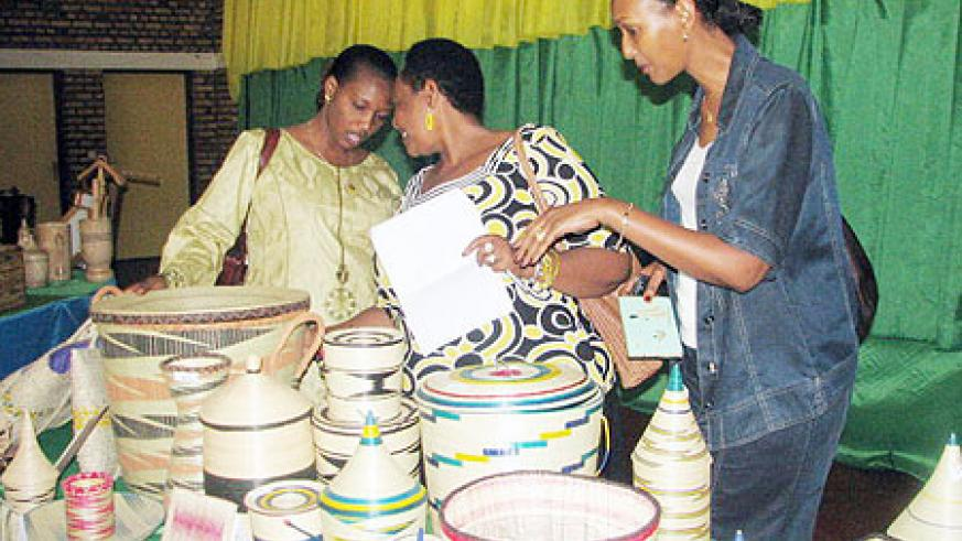 Members of the  panel of judges for the artist competition inspecting some of the items submitted for the competition. (Photo: J.C Gakwaya)
