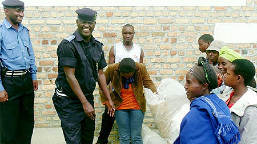 Ruhango Police Commander Supt. Fred Simugaya receives the collected polythene bags from residents. (Photo: D. Sabiiti)