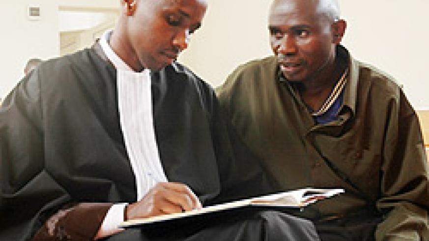 DENIED BAIL: Capt. Jean Marie Vianney Karuta (R) with his lawyer in court last week (File photo)