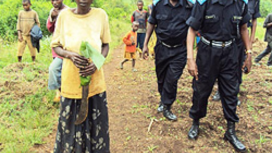 Marie Nyiramungu with the machete she used to kill her children and husband, as the police escorts her from her hide out  to a waiting Police vehicle.