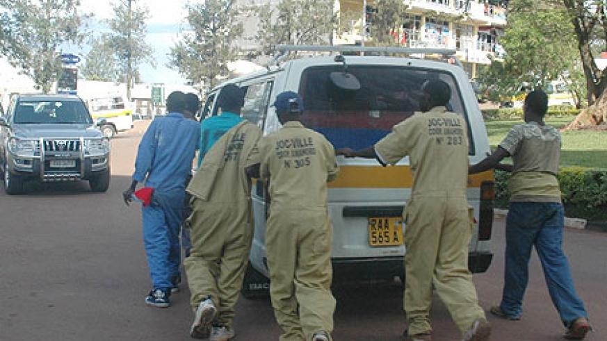 Members of one of the casual labourers cooperatives pushing a mechanically faulty minibus. KCC has lauded their contribution (File Photo)
