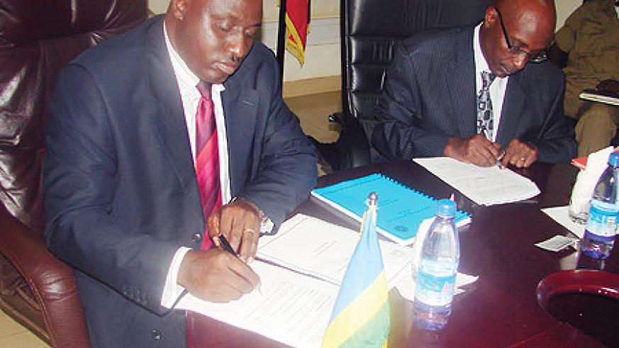 Rwanda's Commissioner General of Police, Emmanuel Gasana, and his Ugandan counterpart sign an MoU in Kampala yesterday (Photo: E. Kabeera)