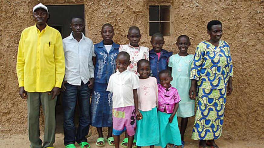 Valens Ntakirutimana (extreme left) stands infront of his house with the family. (Photo by Sarah Boseley, The Guardian UK)
