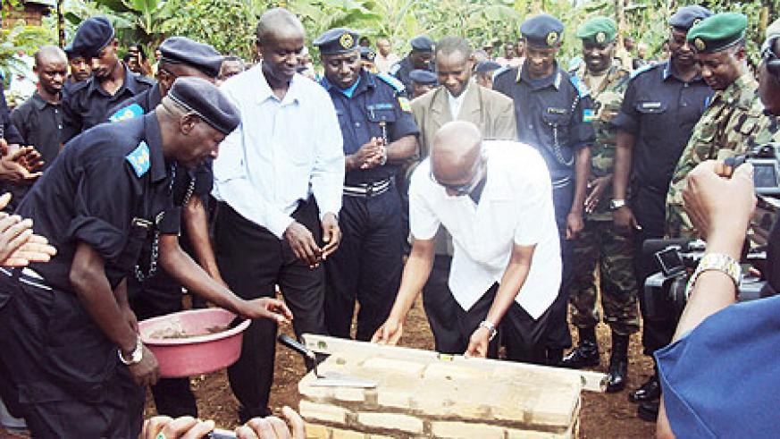 Minister Fazil Harerimana (R) and Empraim Kabaija lay a foundation stone at the first house built as Police officers look on. (Photo; S. Rwembeho)
