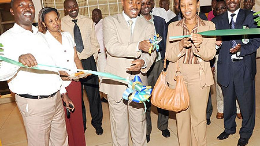 Deputy Commissioner General of Rwanda Revenue Authority Eugene Torero (C) with Molly Rugambwa of the Private Sector Federation opening the RRA Nyabugogo Branch. (Photo / J. Mbanda)