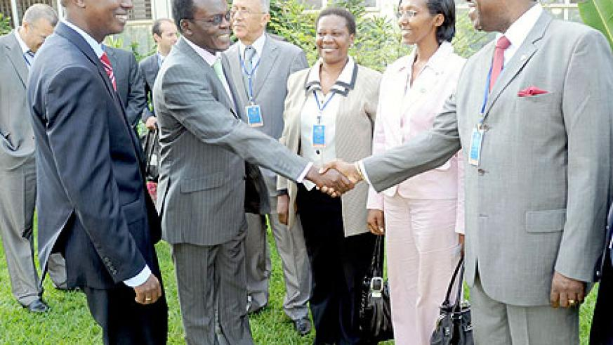 The Secretary General of Union of Producers, Transporters and Distributors of Electric Power in Africa (UPDEA) Eng. Tella Abel Didier (R) greets the General Manager Kenya Electricity Transmission, Joe Ager ,as State Minister Colette Ruhamya (2nd right) an