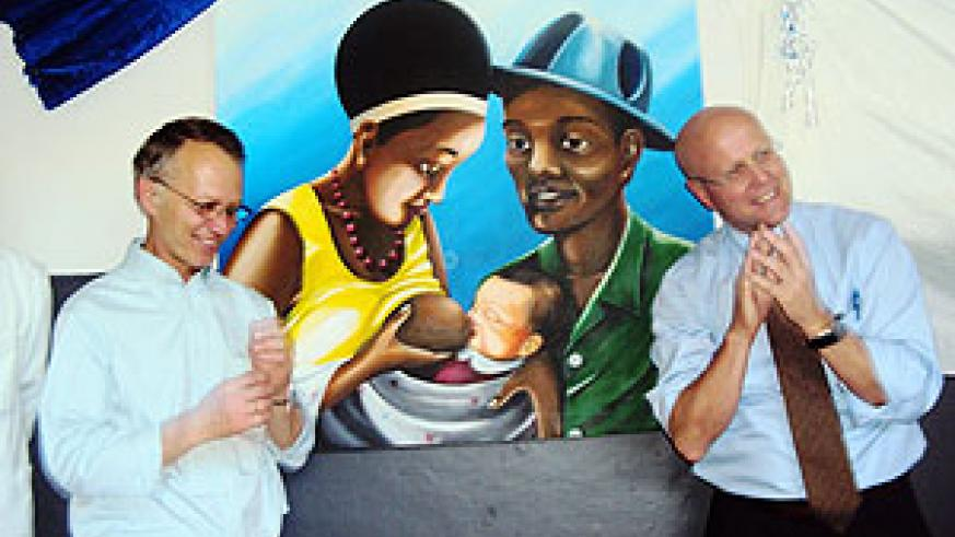 Dennis Weller (R) and Charles Lyons unveiling a  painting depicting some of the intervention measures offered at Nzige Health Center. Photo S. Rwembeho.