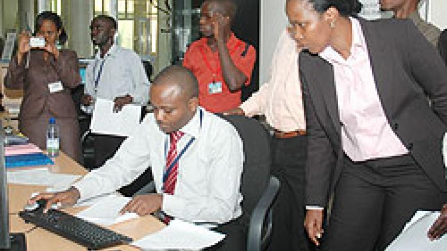 RDB's COO Clare Akamanzi look on as Yves Sangano, the Director of Business Registration explains how the system works (Photo; F. Goodman)