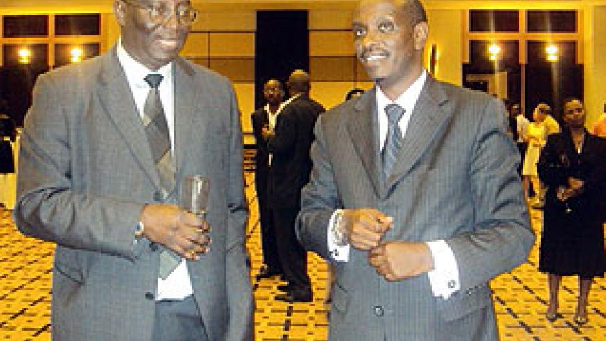 The outgoing WHO Country Representative, Dr. Jack Abdoulie (L) chats with the Minister of Health, Dr. Richard Sezibera (R) during the farewell ceremony
