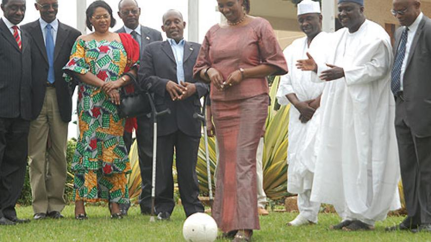 Speaker Rose Mukantabana kicks a ball to mark Rwanda's joining of parliamentary network on MDGs. Looking on are Rwandan and  Nigerian MPs