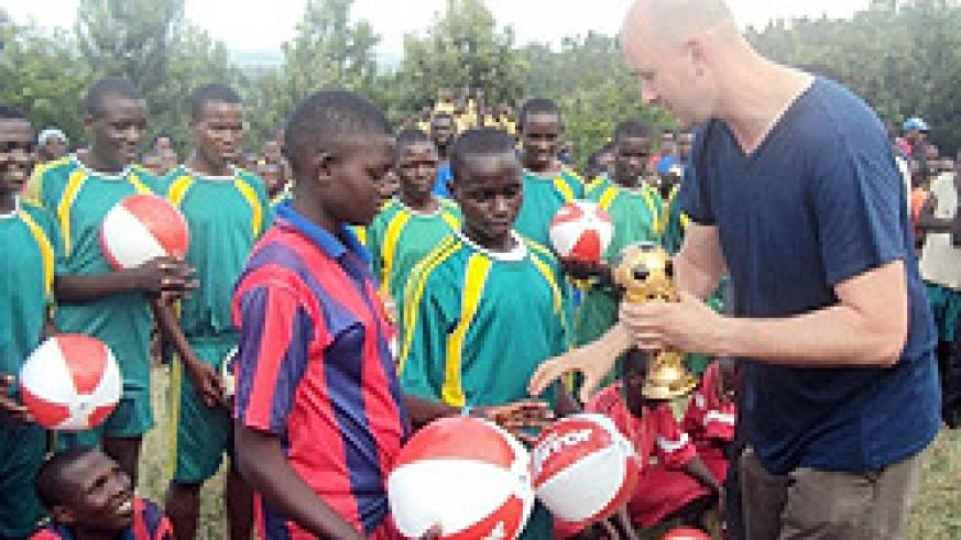 UK's Daily Mirror reporter, Ryan Parry handing over a trophy to a winning team of the tournment organized as part of the newspaper's outreach programmes in Rwanda. (Photo: D. Ngabonziza)