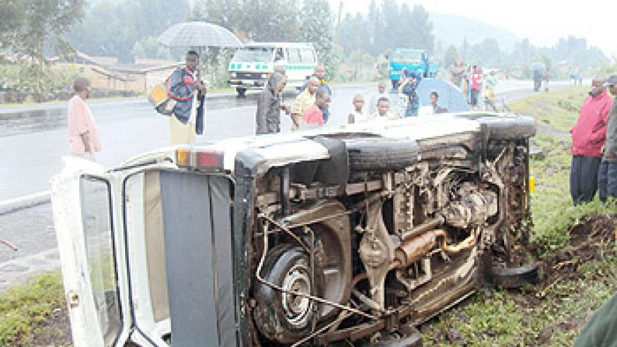 Curious residents staring  at the minibus which overturned after the accident. (Photo: B. Mukombozi)