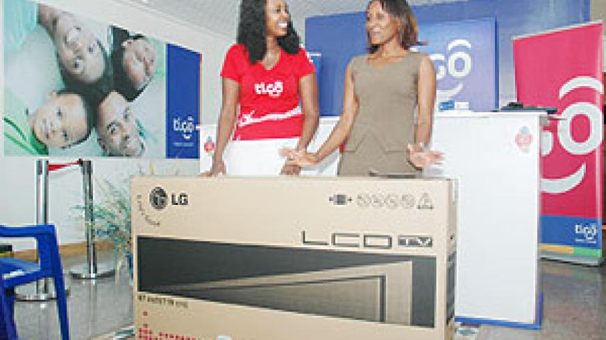 A delighted Uwera Gloriose (Right) flanked by Tigo's marketing manager Nina Claudia Ndabaneza shortly after receiving her LG flat screen at Tigo Tower yesterday. (Photo F. Goodman)