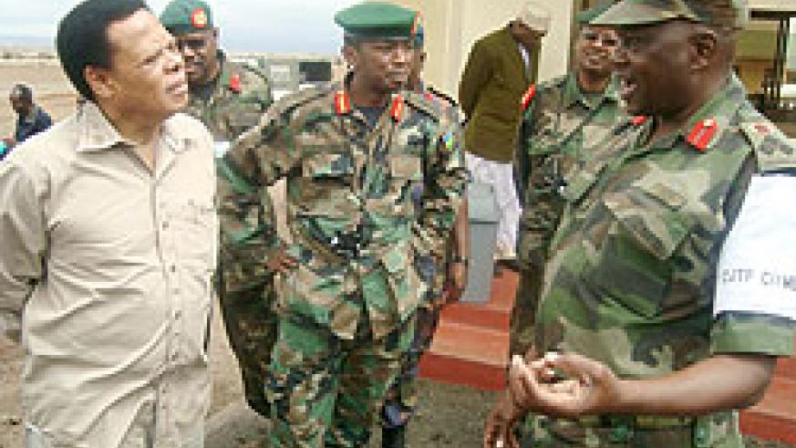 A Ugandan army officer addressing Juma Mwapachu during his visit to a joint regional military exercise in Tanzania last year as Rwanda's Brig. Gen Norbert Kalimba (C) looks on (File photo)