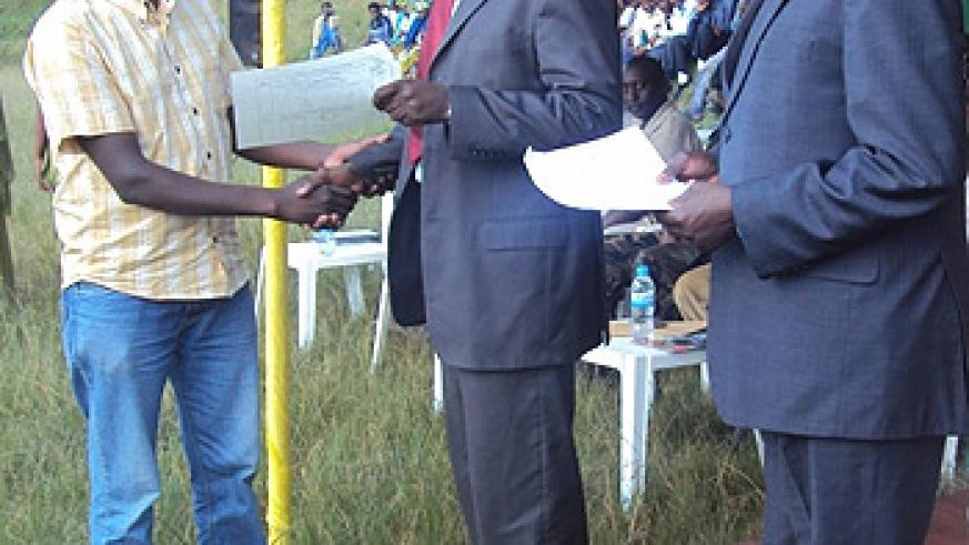 The Minister of Environment and Natural Resources, Stanislas Kamanzi handing over a land registration certificate to one of the residents (Photo; F. Ndoli)