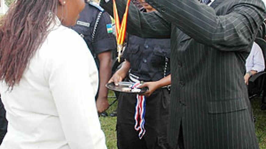 State Minister, Dr Mathias Harebamungu, awarding one of the students with a medal at the Police headquarters yesterday (Photo F Goodman)