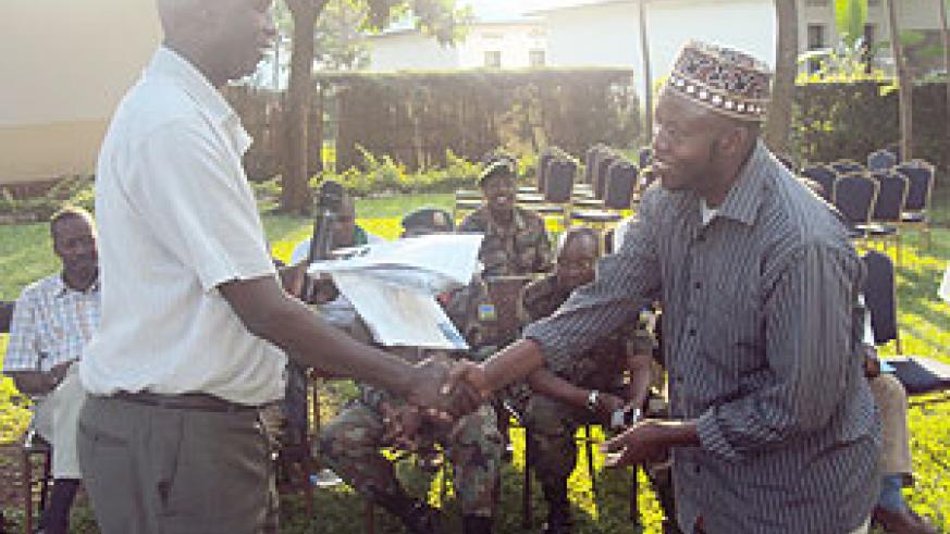 Governor Ephraim Kabaija handing over motorcycle keys to Hussein Ruhumurambuga. (Photo: S. Rwembeho)