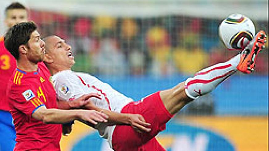 Switzerland's midfielder Gokhan Inler clears the ball under pressure from Xabi Alonso.