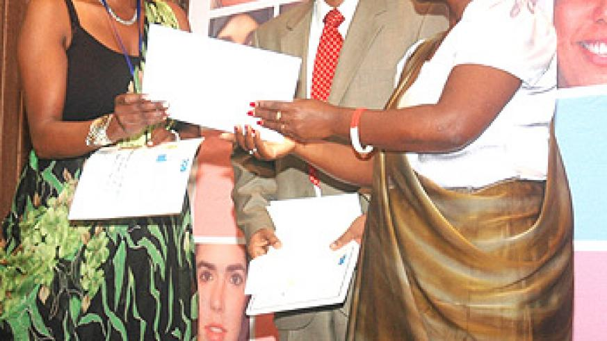 Urayeneza Musoni Charlotte receives a certificate for her winning business plan from the Hon. Monique Nsanzabaganwa as Dr. Satya Murty looks on (Photo. F. Goodman)
