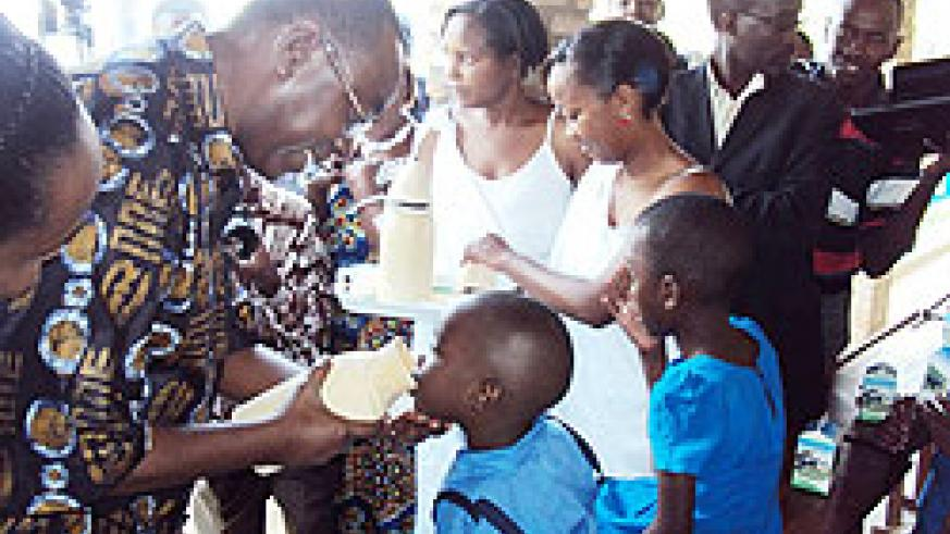 Prime Minister Bernard Makuza feeds a child with milk in Musambira sector yesterday . (Photo; D. Sabiiti)