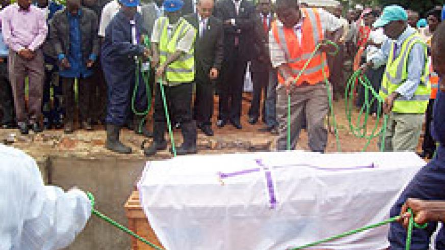 Caskets containing remains of Genocide victims being lowered into mass graves at the Ggolo site in Uganda yesterday (Photo G Muramira)
