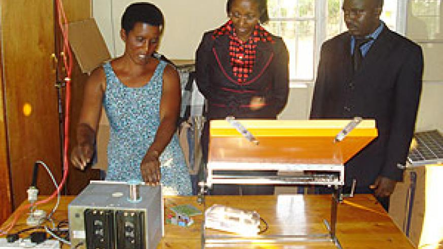 Nyirasengimana, head of the women's solar association in Bugesera District, demonstrates to Minister Collette Ruhamya how solar energy equipment operate. (Photo by Ivan R)