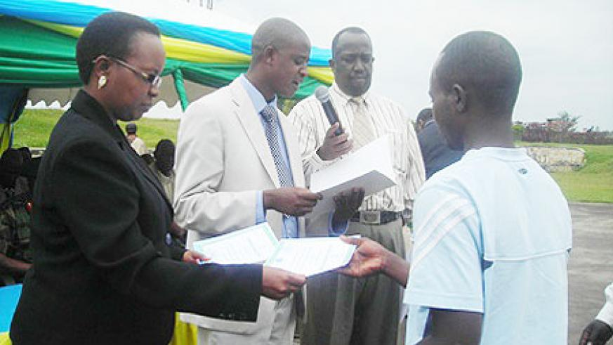 The Permanebt Secretary in the Ministry of education handing over a certificate to graduands. (Photo J Gakwaya)