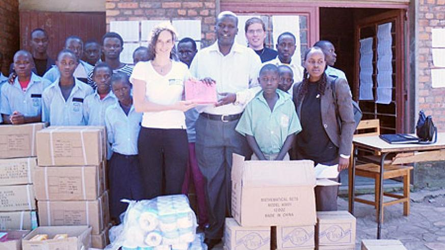Jason Rugero, head of Nkundabana children centre with the childern recieve the donation from Esther Kronsbein, Country Coordinator HHN Rwanda. Photo G. Mugoya