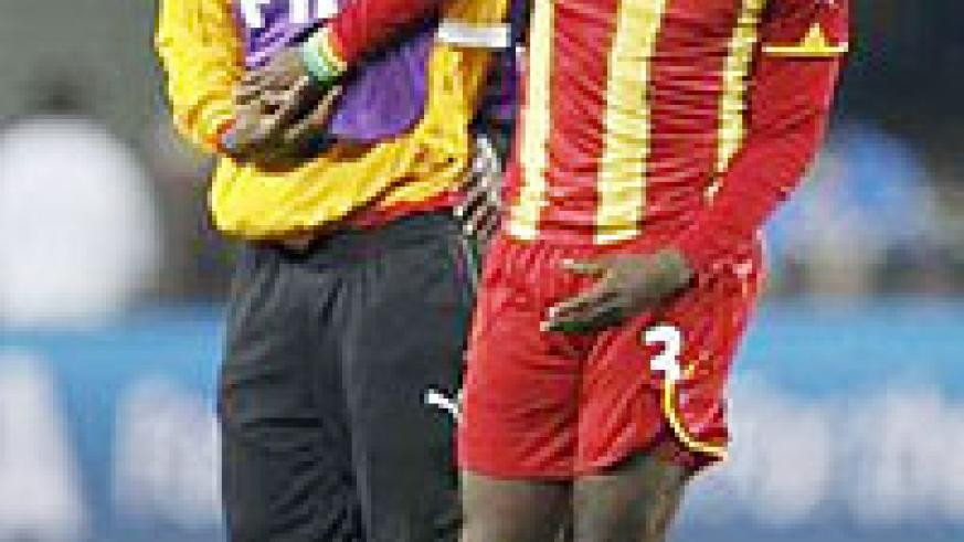 Ghana's Asamoah Gyan (R) is consoled after the 2010 World Cup quarter-final soccer match.
