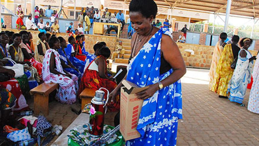 One of the women volunteers receiving a motivation package from World Vision on Tuesday. (Phot by I. Mugisha)