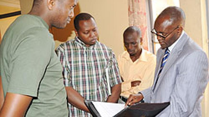 Augustin Nkusi (R) talking to journalists after yesterday's press conference (Photo; J. Mbanda)