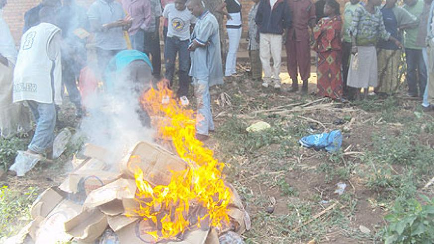 Residents of Rwamagana witnessing the burning of the alcohol. (Photo: S. Rwembeho)