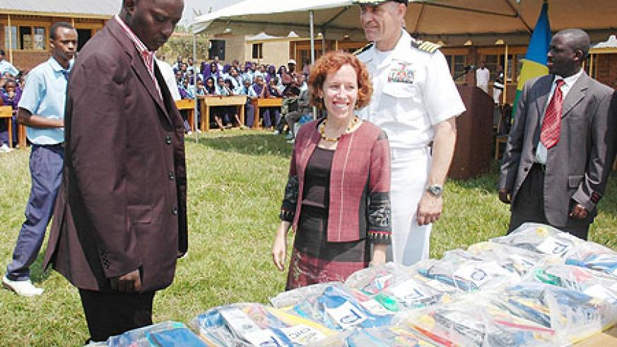 The Charge d' Affairs of the US Embassy, Anne Casper and Kicukiro Mayor, Jules Ndamage, inspecting the scholastic materials as Capt. Scott Vasina looks on (Photo: F. Goodman)