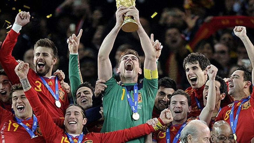 Spain captain Casillas holds the World Cup trophy aloft as ticker tape falls at Soccer City.